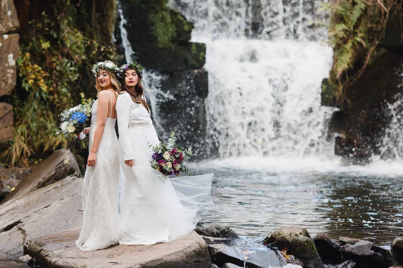 Two models stood on rock in front of waterfall