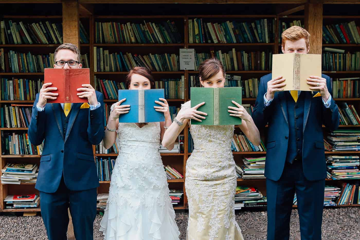 joint wedding four people covering faces with books