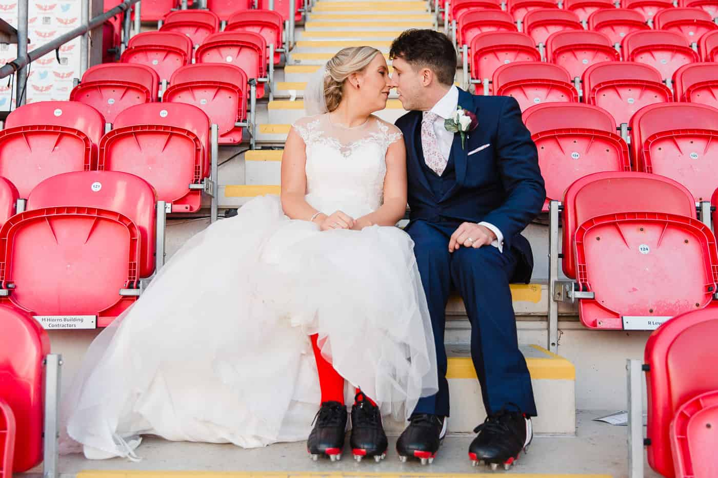 two people sat down in rugby stand kissing