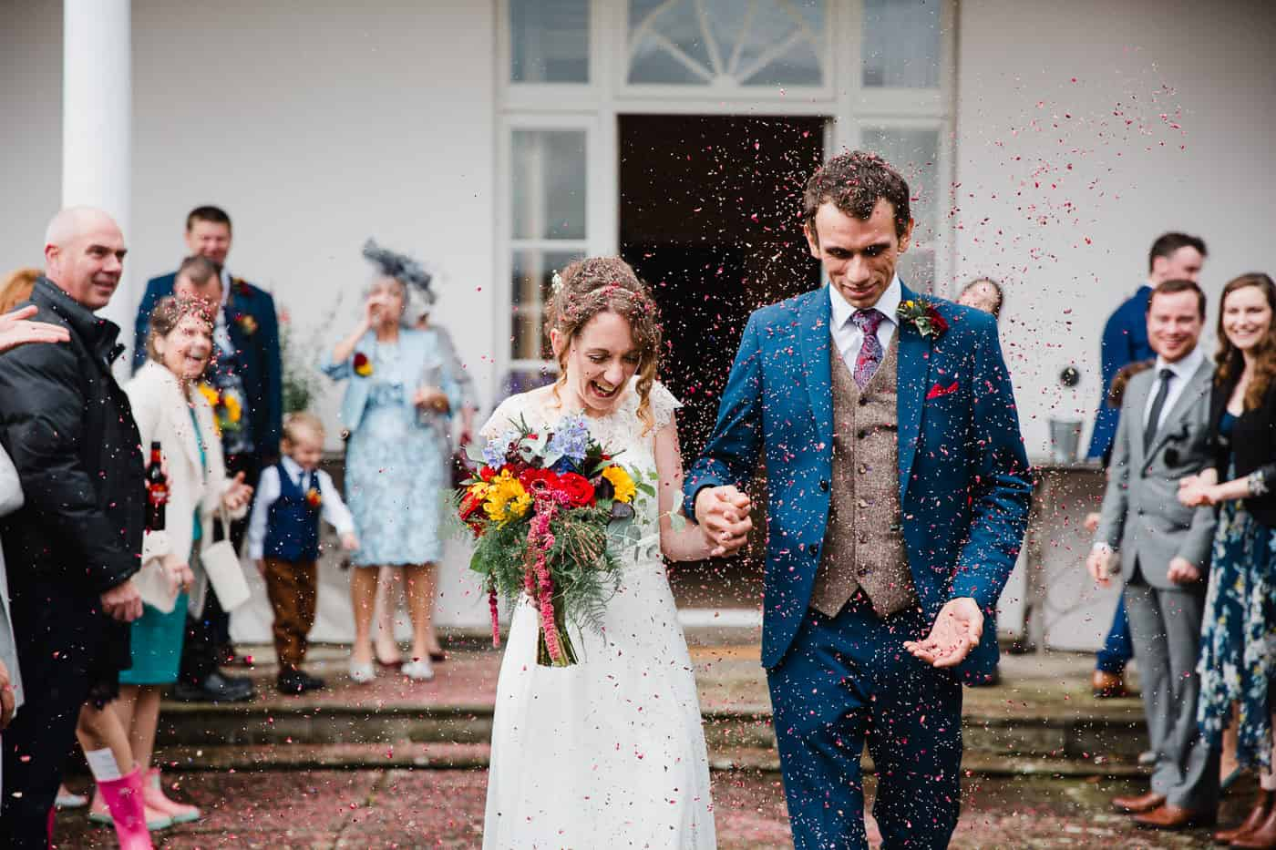 two people smiling holding hands walking through confetti