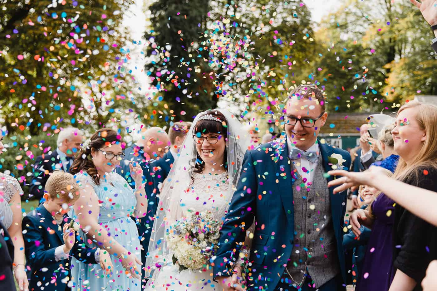 two people smiling walking through confetti