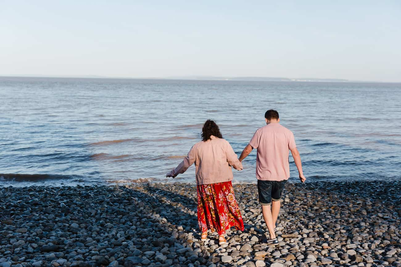 two people walking onto a beach