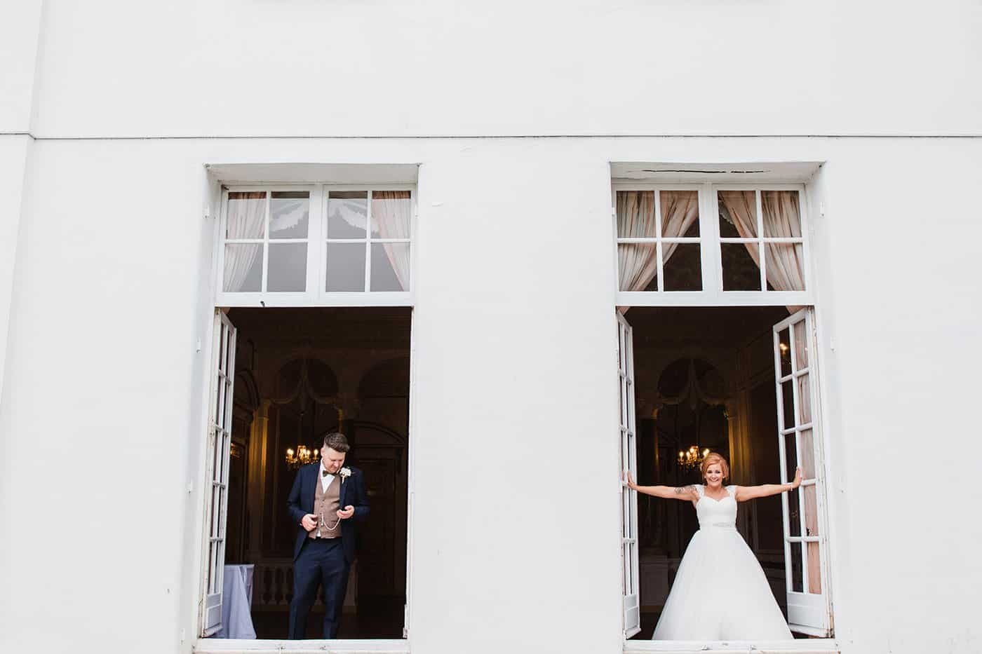 bride and groom stood separately in window