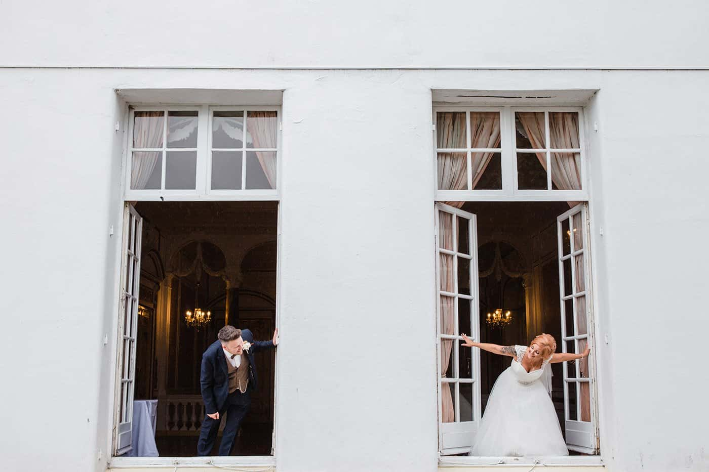 bride and groom looking at each other from two different windows