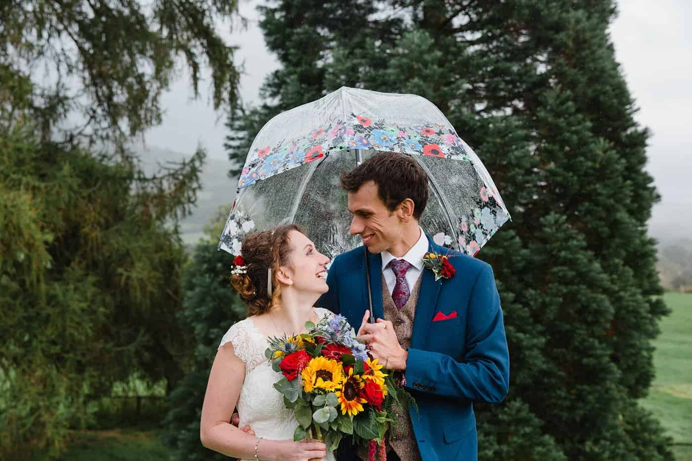 bride and groom under an umbrella laughing