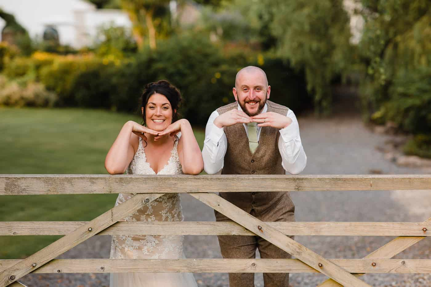 bride and groom leaning on wooden gate