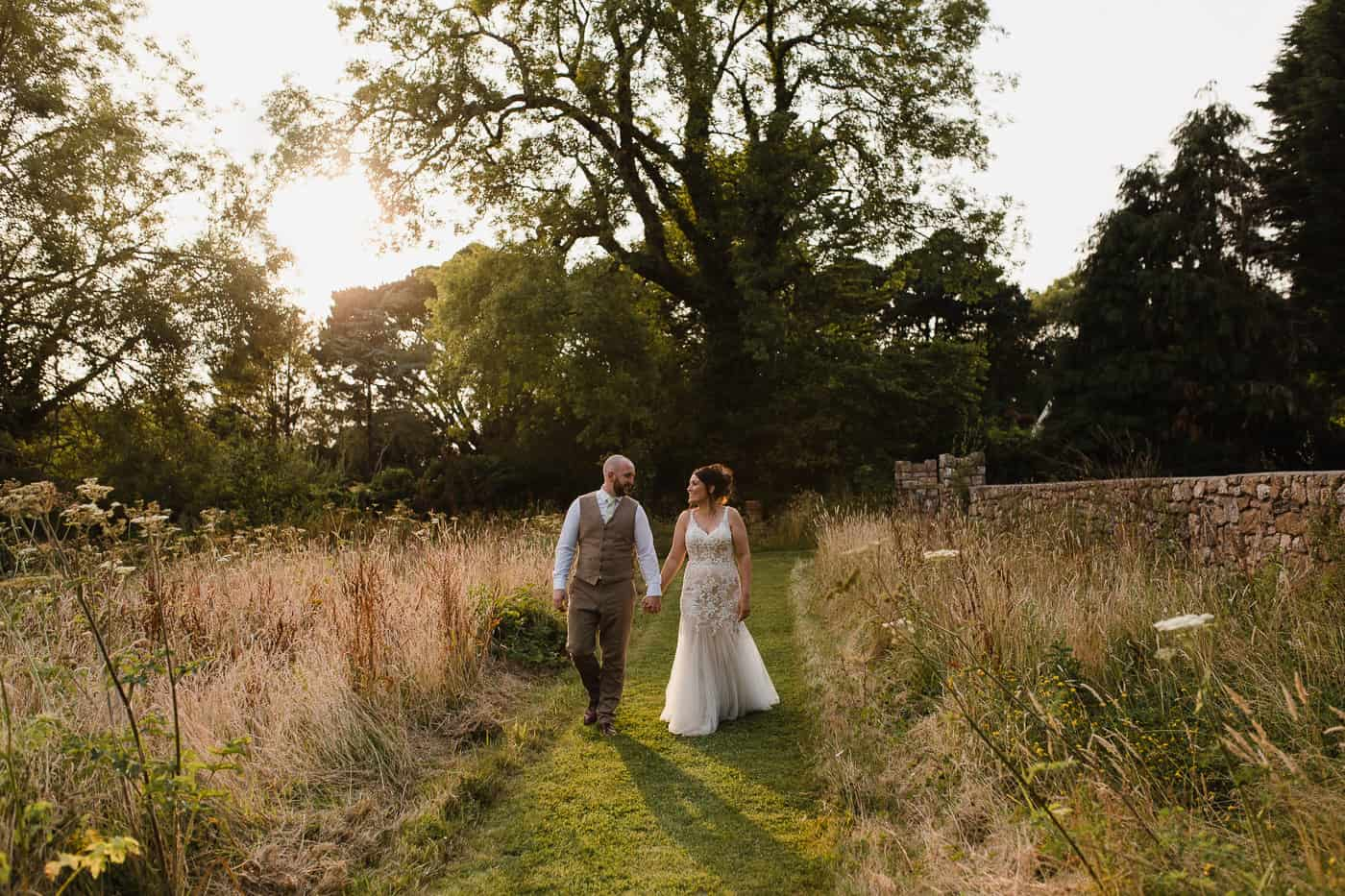 bride and groom walking at golden hour