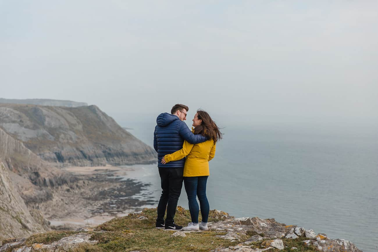 couples portrait on clifftop facing sea