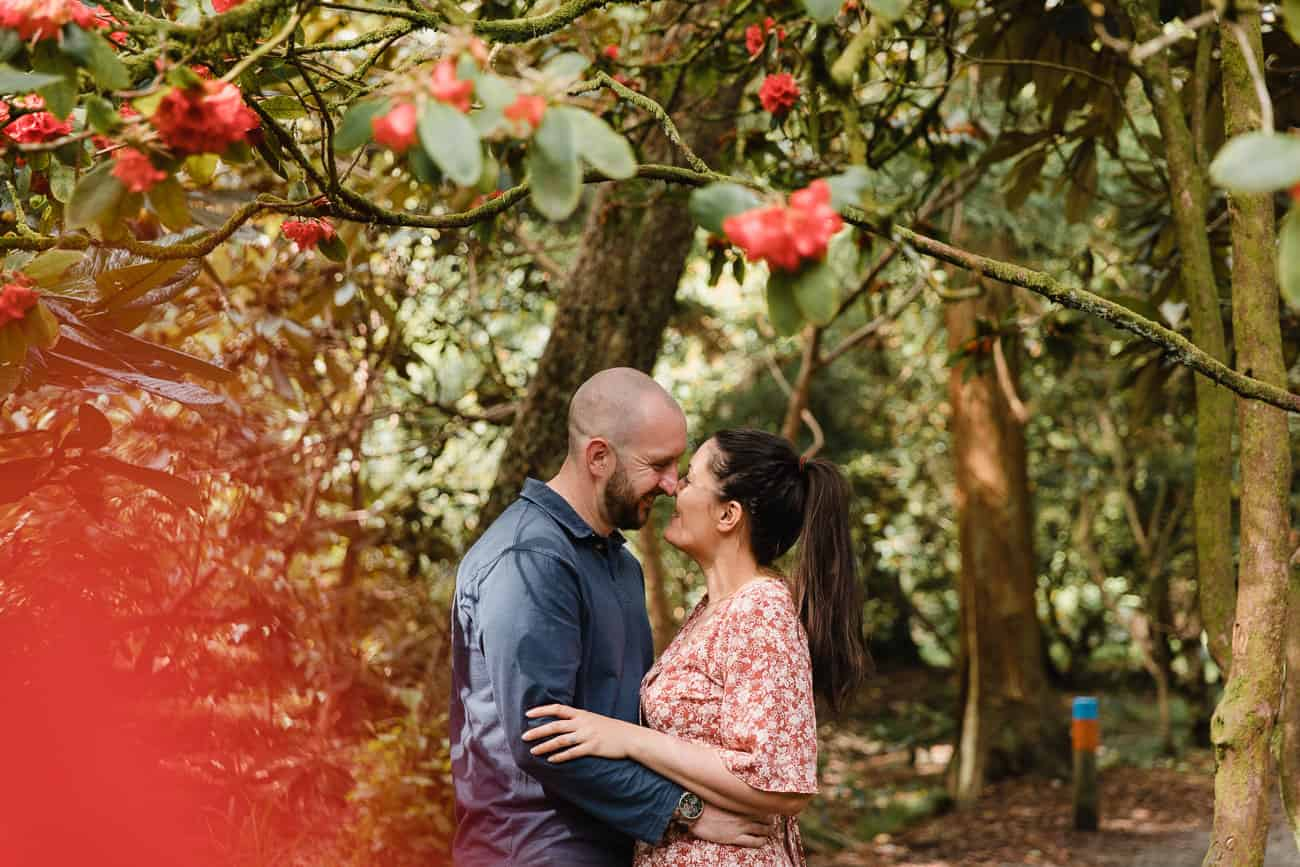 couple close together under red flowers