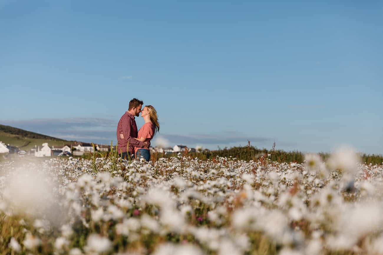 couple in wild flowers kissing