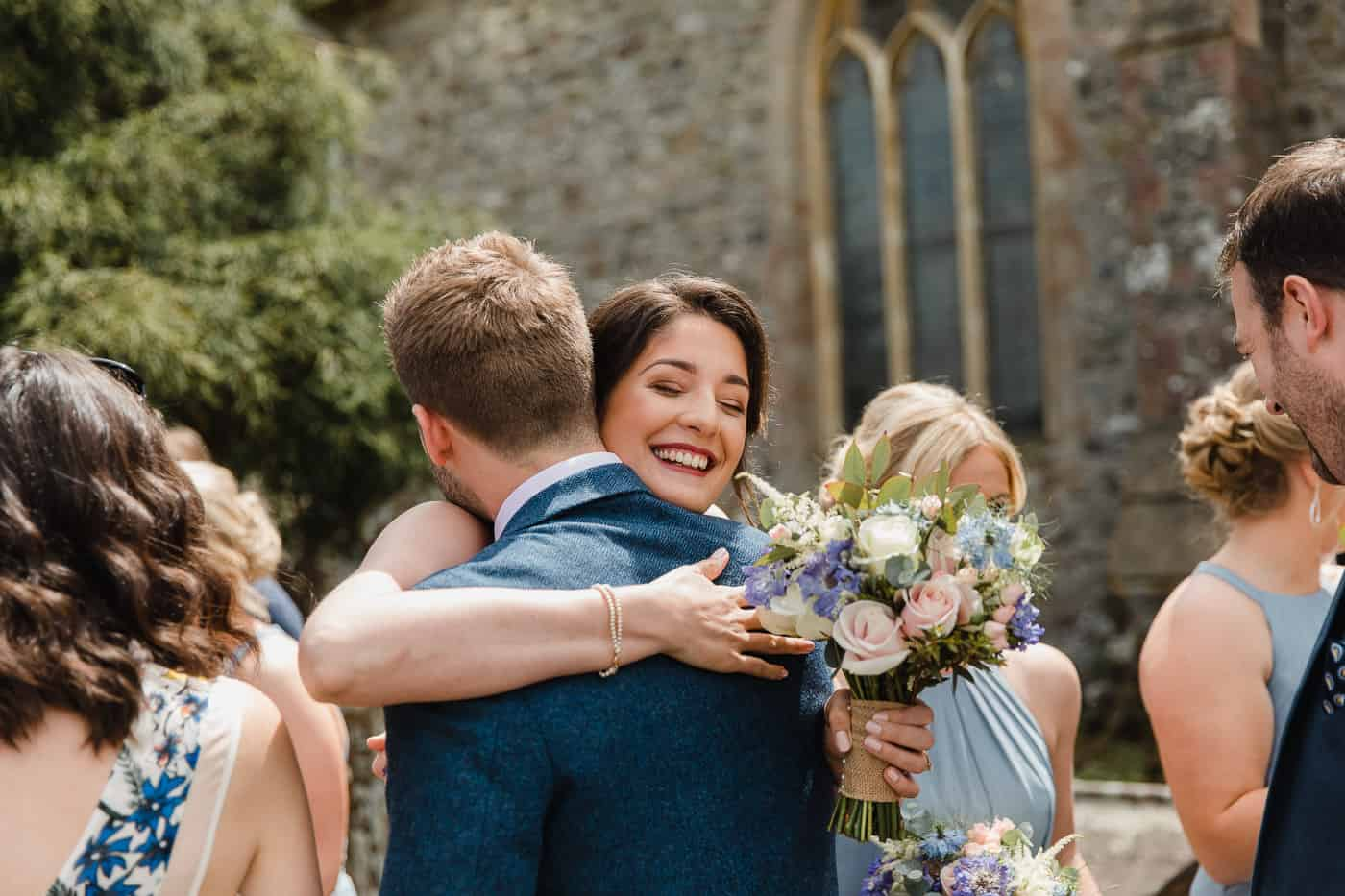 wedding guests hugging outside church South Wales