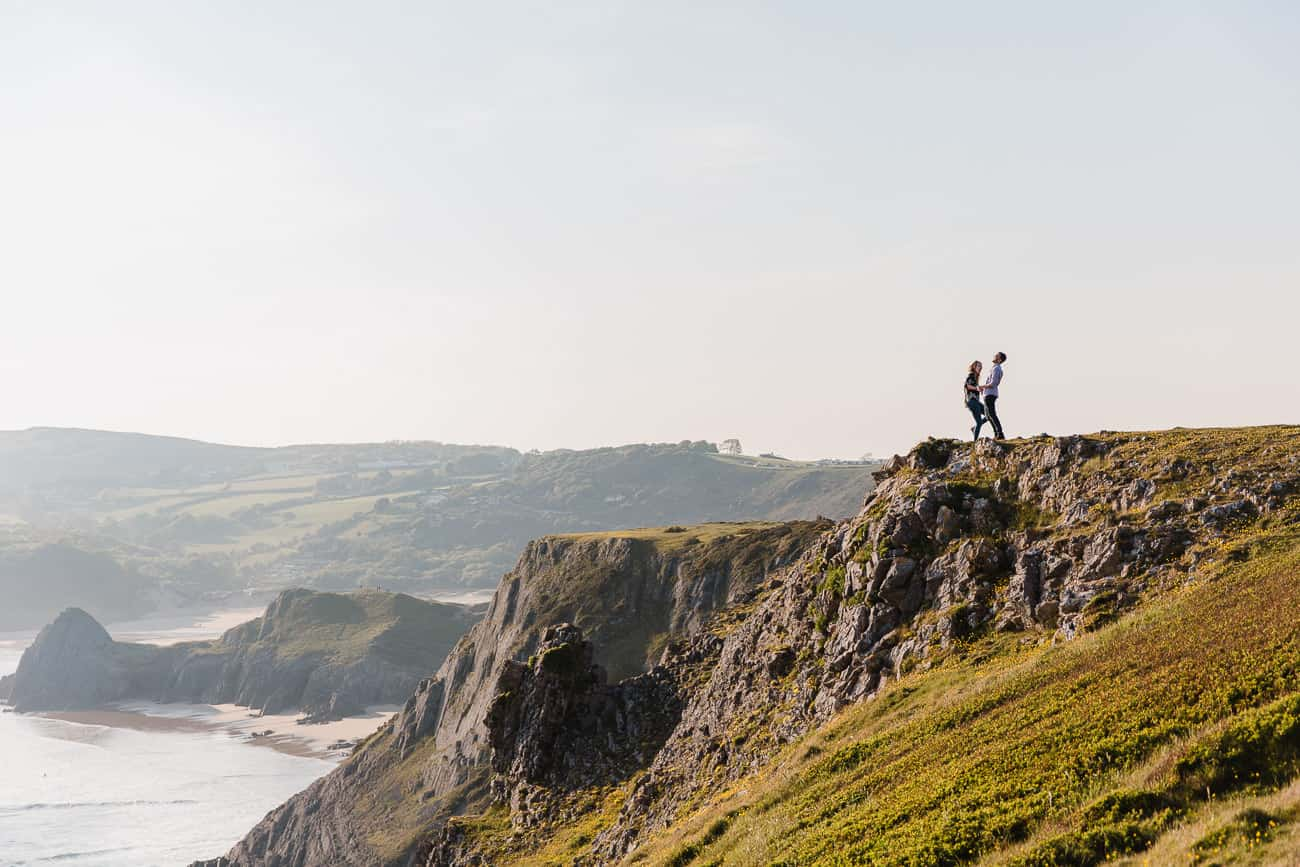 couple at a distance laughing on a clifftop