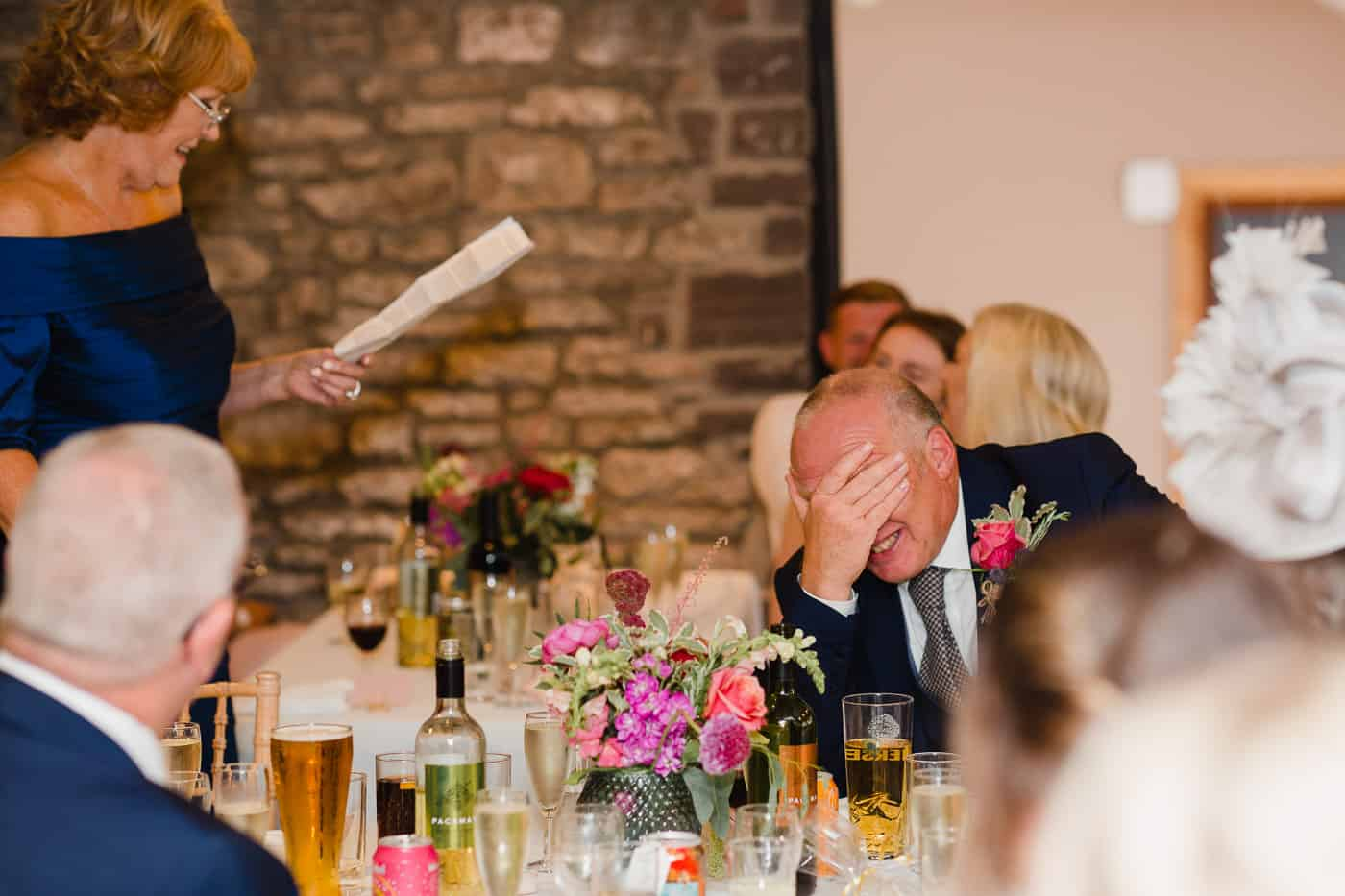 father of brides hand on face during wedding speeches