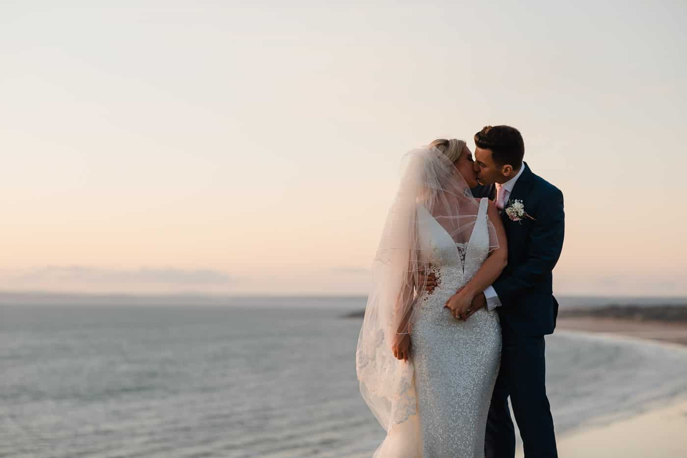 bride and groom at golden hour overlooking sea and kissing