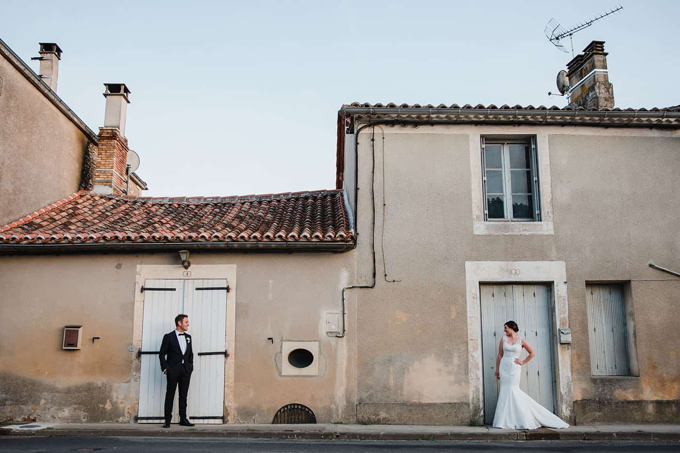 bride and groom in front of two doors looking over at each other