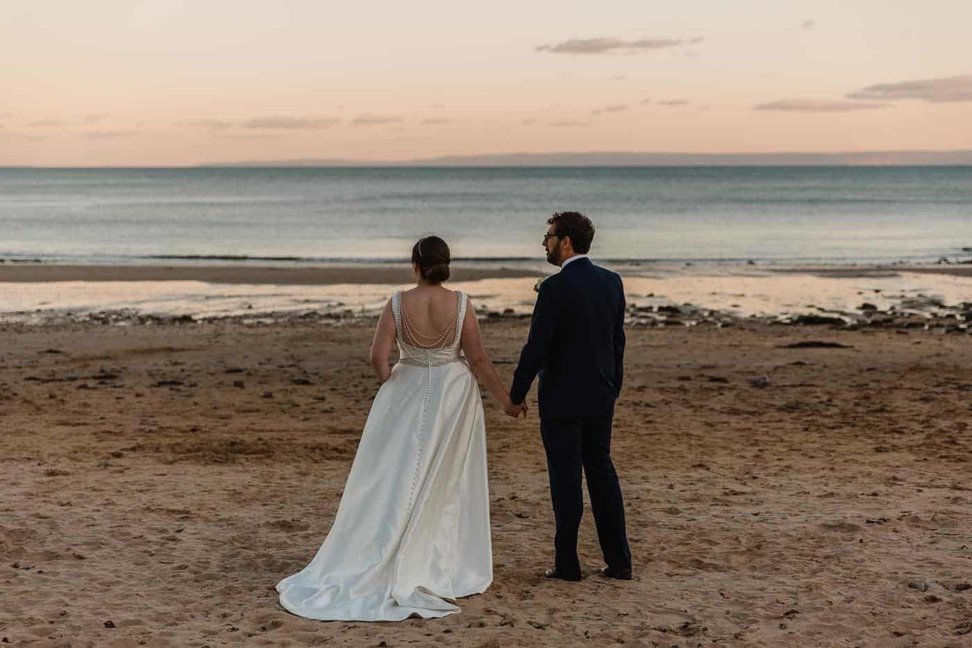 bride and groom looking out to sea