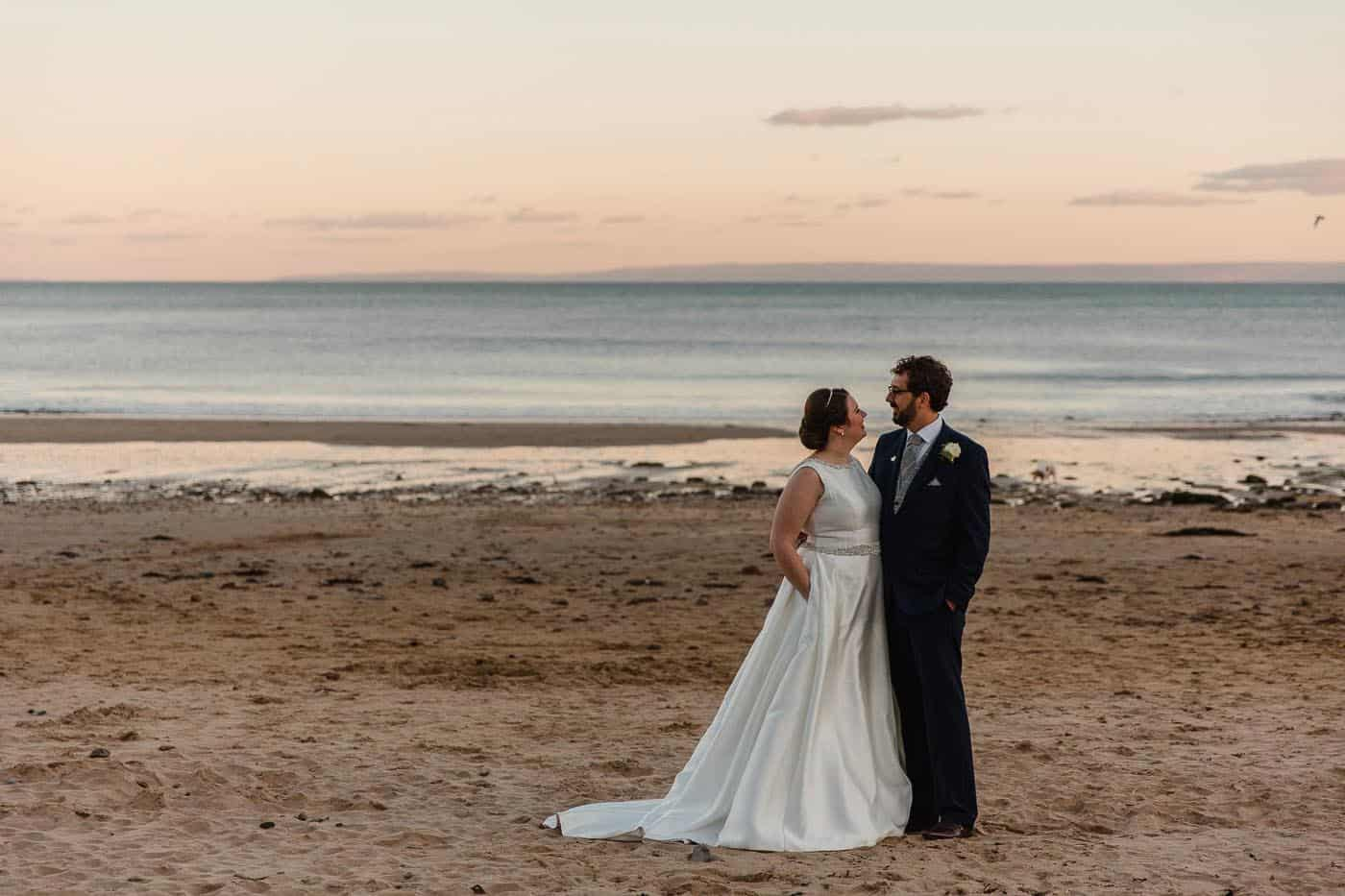 bride and groom on beach looking at each other