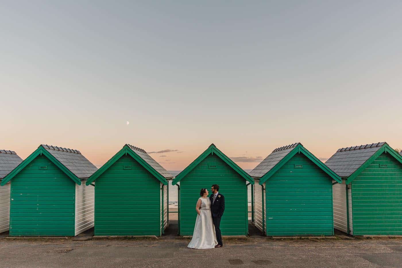 bride and groom in front of beach huts