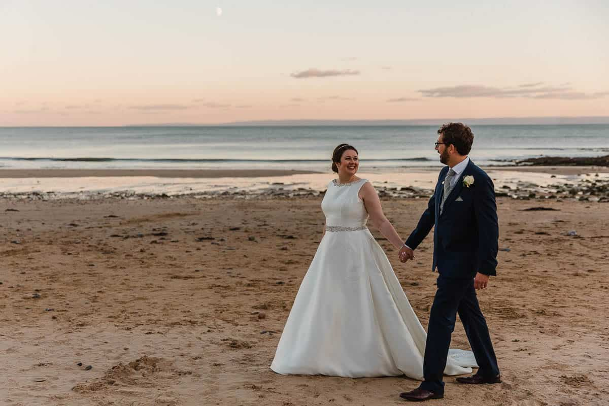 bride and groom walking along langland bay